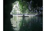 Woman kayaks near cave in Rock Islands, Palau, Micronesia.