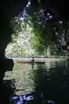 Woman kayaks near cave in Rock Islands, Palau, Micronesia.