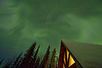 Northern lights (aurora) over roof of house near Fairbanks, Alaska, during February
