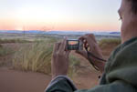 Man photographs dawn at Sossusvlei, sand dune area in south central Namibia.