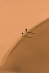 Man and woman walk atop sand dunes of Sossusvlei, Namibia, Africa.