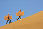 Sandboarding on sand dunes near Swakopmund, a coastal city halfway up Namibia's Atlantic coast.