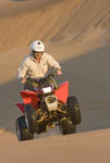 Riding 'quadbike' or ATV on sand dunes near Swakopmund, a coastal city halfway up Namibia's Atlantic coast.