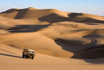 Desert tour vehicle climbs sand dunes at dusk outside Swakopmund, popular tourist town on the coast of Namibia.