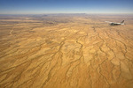 Aerial view of desert landscape of north central Namibia, Africa, with a small airplane in view.