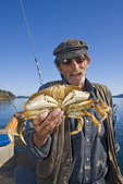 Fisherman holds up freshly caught dungeness crab.