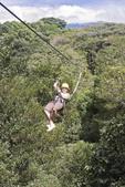 Zipping through rainforest canopy on zipline tour at Buena Vista Lodge in Rincon de la Vieja forest.