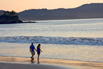 Couple enjoys walking along the beach at sunset, Flamingo Beach, Costa Rica.