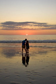 Loving couple enjoys the beach at sunset.