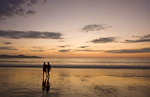 Couple enjoys the beach at sunset.