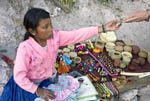 Tarahumara native Indian girl takes money for a basket she is selling at her cliff home just below the Hotel Posada Barrrancas.