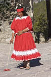 "Native Tarahumara woman demonstrates ""ball race"" where women run while tossing a ring with a stick."