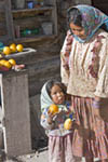 Young mother with her small daughter standing by their simple log cabin home in the Tarahumara village of San Alonso in the Copper Canyon area of Mexico. The Tarahumara are related to Maya Indians and are a shy people who live in Copper Canyon. Many still wear traditional clothing and live a simple life, often without electricity or modern conveniences.