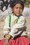 Young girl sits by her simple adobe and log home in the Tarahumara village of San Alonso in Copper Canyon, Mexico.