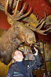 Man 'feeds' a beer to a trophy moose on the wall at the Shooting Star Saloon in Huntsville, Utah.