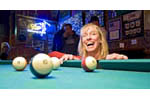 Woman has fun at pool table in Shooting Star Saloon in Huntsville, Utah.