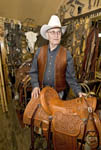 Glen Thompson, elderly saddle maker, shows off one of his hand made saddles in his shop in Eden Utah.
