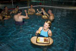 Woman enjoys cheese and meats on floating tray during apres ski in heated swimming pool at Burgerbad, Switzerland.