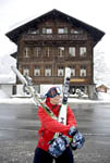 During heavy snowfall, skier carries skis at the end of a day skiing at Grindelwald, Switzerland.