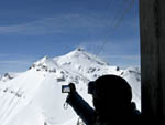 Visitor uses digital camera to photograph the Piz Gloria revolving restaurant at the top of the Schilthorn ski area.