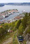 Fløibanen funicular car makes its way up the mountain with the waterfront and harbor of Bergen, Norway, in view.