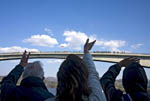 Passengers at bow of MS Trollfjord wave to people who line the tall bridge spanning the narrow sound of Stokksund along the coast of Norway.