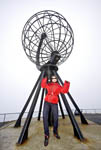 Young woman celebrates with glee at the globe at North Cape, Norway at 71 degrees, 10 minutes North.