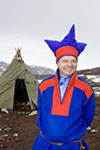 Middle aged Sámi man in traditional clothing stands by his tent and talks about the life of his people at his camp near the Norwegian town of Kjøllefjord.