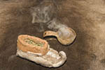 Sámi footwear made of reindeer hide and stuffed with grass for insulation along with a gourd of steaming reindeer broth.