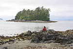 Woman enjoys view of small island in the Broken Group Islands of Pacific Rim National Park of Vancouver Island, Canada.