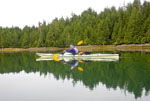 Woman's reflection shows while kayaking in still waters during early morning in the Broken Group Islands of Pacific Rim National Park on the west coast of Vancouver Island, Canada.