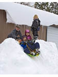 Father and children play with sled, sliding down gentle, short slope at the side of a building near the shore of South Lake Tahoe, California, USA.