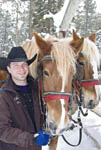 Sled driver poses with two of his horses at a corral that takes tourists on sleigh rides, South Lake Tahoe, USA.