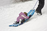 Children sled down short slope in winter, South Lake Tahoe, California, USA. Here an adult pulls a young girl up the hill.