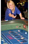 Scene on gaming floor of casino: excited woman throws dice at craps table. South Lake Tahoe, Nevada, USA.