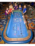 Scene on gaming floor of casino: excited woman throws dice at craps table while friends cheer her on. South Lake Tahoe, Nevada, USA.