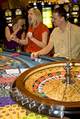 Scene on gaming floor of casino: excited players bet as roulette wheel spins, South Lake Tahoe, Nevada, USA.