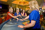 Scene on gaming floor of casino: Excited players at blackjack table.
