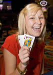 Scene on gaming floor of casino: Excited woman at blackjack table holds winning hand that adds up to 21 points.