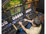 Scene on gaming floor of casino: Man at slot machines in gambling resort, South Lake Tahoe, Nevada, USA.