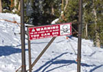 Sign warns skiers that leaving the patrolled 'on slope' area of the ski resort can be dangerous. This terrain is open to skiers but it is at their own risk. Heavenly Mountain Resort, Nevada, USA.
