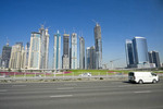Dubai, UAE, skyline seen from freeway with construction cranes atop buildings.