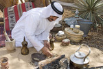 Bedouin man in Arab dress roasts coffee as it was done in the days before modern amenities.
