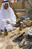 Bedouin man in Arab dress roasts coffee as it was done in the days before modern amenities. Here, he tosses coffee beans in the air as he roasts them over a fire.