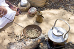 Bedouin man in Arab dress roasts coffee as it was done in the days before modern amenities. Here, he roasts coffee beans over a fire.