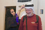 Arab woman in Muslim hijab dress is putting the traditional Arab man's head gear on a visiting western man.