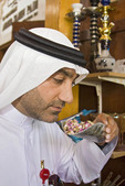 Arab man sniffs flower buds & spices in Dubai souk (old markets).