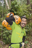 Man shows off zipline helmets at canopy tour