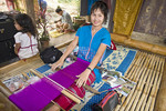Young Thai woman weaves colorful cloth with her young daughter