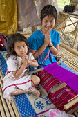 Young Thai woman weaves colorful cloth with her daughter